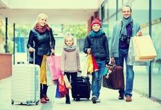 运载购物袋的游人家庭  免版税库存图片