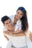 运载他的女朋友肩扛的快乐的英俊的人 免版税图库摄影