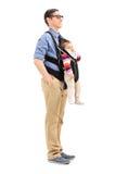 运载他的小女儿的年轻父亲 免版税图库摄影