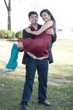 运载他的未婚夫的年轻愉快的印地安人 免版税库存照片
