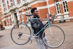 运载他的自行车的骑自行车者 免版税图库摄影