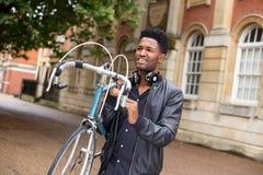 运载他的自行车的骑自行车者 免版税库存照片
