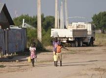 运载水,南苏丹的孩子 免版税图库摄影