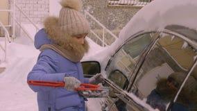 运输、冬天、天气、人和车概念-从汽车的少女孩子清洗的雪有刷子的 股票录像