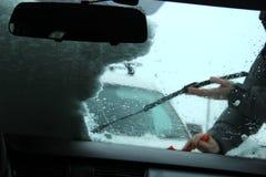 运输、冬天、天气、人和车概念-供以人员从汽车的清洁雪有刮板的 在人` s的洗气器 免版税库存图片