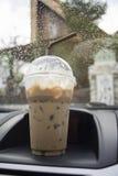 运输和车概念-拿走在一辆汽车的一个前面控制台上把放的杯子被冰的咖啡有水滴的雨水 免版税图库摄影