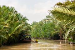 运输在一条小船的年轻工人椰子在河 库存图片