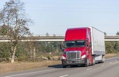 运输在干燥搬运车半拖车的明亮的红色大半船具卡车商业货物运行在有过桥的路 库存图片