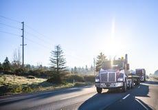 运输在平床半拖车的红色大船具天小室半卡车商业货物运行在半前面卡车护卫舰  免版税库存图片