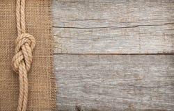 运输在木头和粗麻布纹理背景的绳索 库存照片