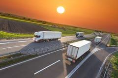 运输在行动迷离的卡车在高速公路在日落 免版税库存照片