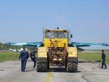 运输在跑道的大黄色拖拉机军事战斗机 免版税库存照片