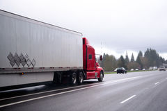 运输在高速公路的红色现代半卡车货物拖车 免版税库存图片