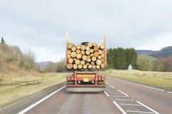 运输堆积了在平脊卡车卡车的切好的木头日志可再造能源 免版税库存图片