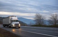 运输大块的白色大船具半卡车用转动盖了半驾驶在晚上湿下雨的路的拖车在车灯 免版税库存照片