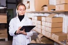 运输推车纸板盒的女工 免版税库存图片