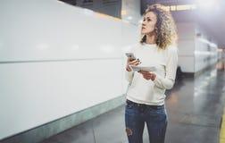 运输的可爱的妇女使用智能手机,当走与在火车站或airpot去的手提行李背包时 库存图片