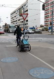 运输的小孩子一辆自行车拖车在红绿灯在交叉点 免版税库存照片