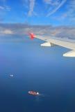 在飞行飞机之下翼的货船  免版税库存图片