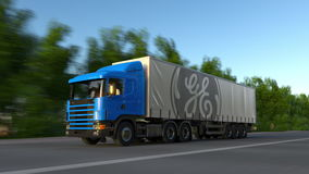 运送半有驾驶沿森林公路的通用电器公司商标的卡车 社论3D翻译 免版税图库摄影