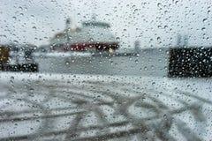 运送在口岸通过在玻璃的雨珠在强的雪 库存照片