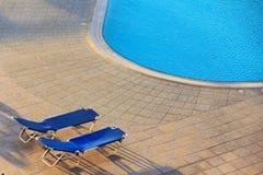 近两把椅子对游泳池 库存照片
