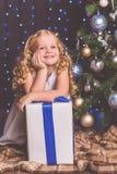 近俏丽的儿童女孩装饰了圣诞树 免版税图库摄影