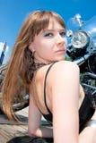 近华美的妇女乘黑色摩托车 免版税库存图片