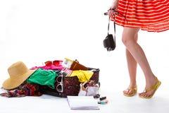 近女孩的腿过度了充填手提箱 免版税库存图片
