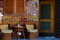 近柳条露台椅子和桌 图库摄影