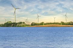 近海处风轮机喜欢绿色可选择的技术和海 免版税库存照片