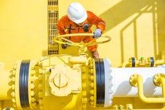 近海油和煤气操作,允许气体的生产操作员开放阀门流动到水平线管子 图库摄影