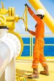近海油和煤气操作,允许气体的生产操作员开放阀门流动到水平线管子 免版税库存照片