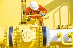 近海油和煤气操作,允许气体的生产操作员开放阀门流动到被送的气体和原油的水平线管子 免版税图库摄影