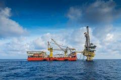 近海油和煤气生产和探险、嫩船具工作在遥远的平台对完成气体和原油涌出 免版税库存图片