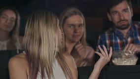 近的位子的粗鲁的男人和妇女谈的干扰的妇女在戏院 免版税库存图片