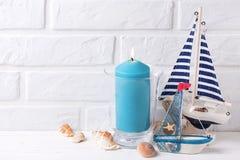近蓝色灼烧的蜡烛、装饰小船和海星由whi 库存照片