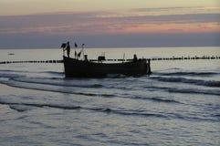返回从海的小船的渔夫 免版税库存图片
