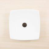 这一个黑暗的巧克力按钮和小白方块盘 免版税库存图片