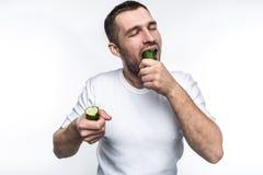 这个人喜欢吃自然和有机水果和蔬菜 在这张图片他有一个长的黄瓜两个片断  免版税图库摄影