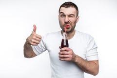 这个人喜欢快餐非常和甜点饮料  他喝着从瓶的焦炭高兴地 修改 库存照片