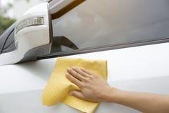 这个图象是抹汽车的图片与一块黄色microfiber布料用人工 免版税库存图片