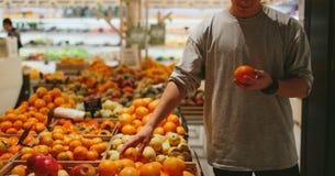 这应该是美好的 英俊的年轻人橙色胡椒和购物袋,当站立在食品店时 免版税图库摄影