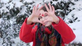 这录影是关于一个年轻白种人可爱的女孩的画象红色外套的在看直接对照相机和摆在的冬天 股票录像