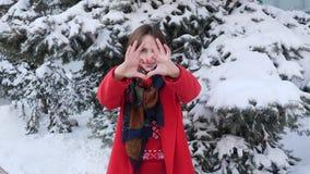这录影是关于一个年轻白种人可爱的女孩的画象红色外套的在看直接对照相机和摆在的冬天 股票视频