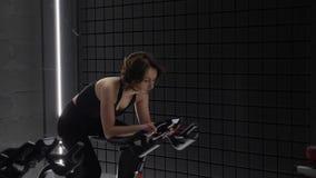 这录影是关于享受她的在锻炼脚踏车的俏丽的可爱的年轻女人侧视图锻炼 俏丽的女孩循环的锻炼 影视素材