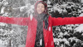 这录影是关于使用与雪的红色外套的美丽的年轻白种人妇女在室外的冬天 影视素材