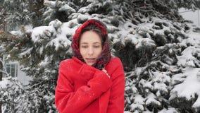 这录影是关于包裹在温暖的红色外套的美丽的年轻白种人妇女在室外的冬天 股票视频