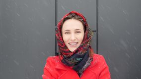 这录影是关于在温暖的红色外套包裹的美丽的年轻白种人妇女微笑对与牙括号的照相机 股票录像