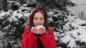 这录影是关于室外红色的外套的美丽的年轻白种人妇女吹在雪对照相机在冬天 影视素材